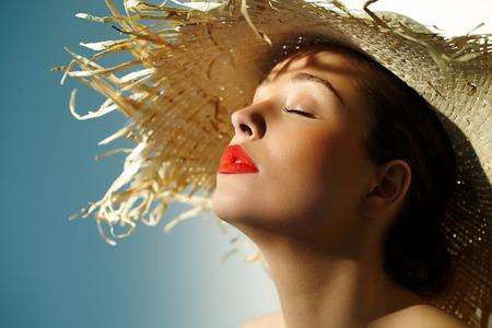 Vrouw draagt strooien hoed en genieten van de zon. Stockfoto