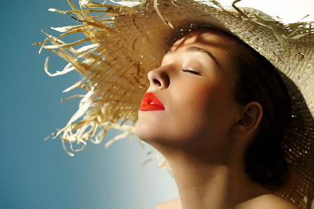 tanned: Woman wearing straw hat and enjoying the sun.