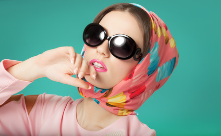 Sixties style beauty girl wearing silk scarf and sunglasses.