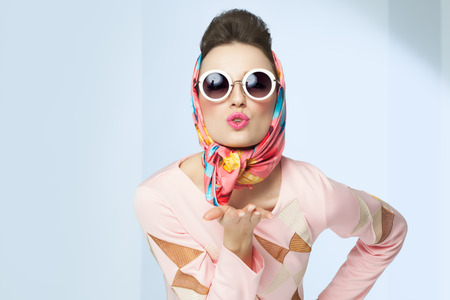 60s fashion: Sixties style girl blowing a kiss. Retro fashion with silk scarf and sunglasses. Stock Photo