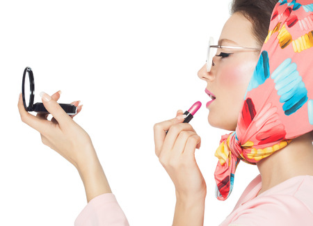 Sixties style girl over white background applying lipstick. photo