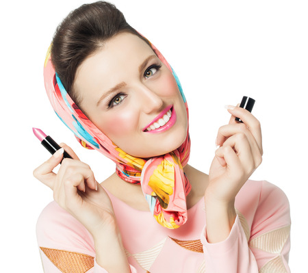 60s fashion: Sixties style girl holding pink lipstick over white background. Stock Photo