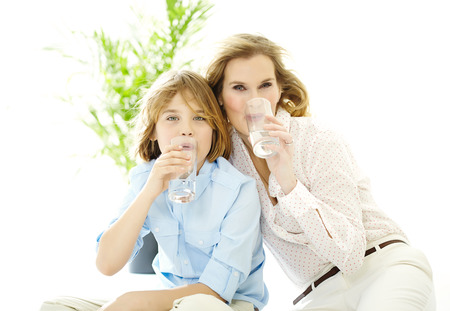 shot glasses: Mother and son drinking water. Stock Photo