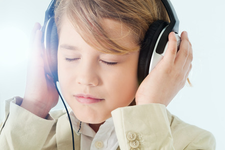 9 10 years: Boy listening to music in headphones with eyes closed.