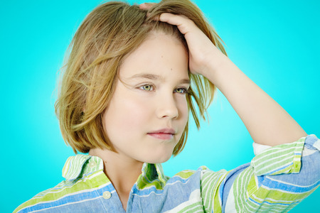 blond boy: Ten year old boy posing on cyan background. Stock Photo
