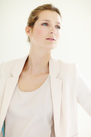 blazer: Young Caucasian businesswoman wearing powder pink blazer posing indoors. Stock Photo