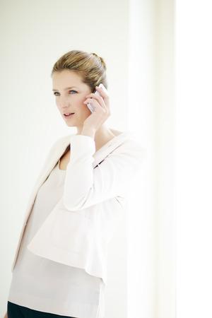 blazer: Young Caucasian businesswoman talking on phone.