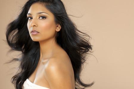 plan �loign�: Belle jeune femme asiatique  indien aux cheveux longs posant sur fond beige