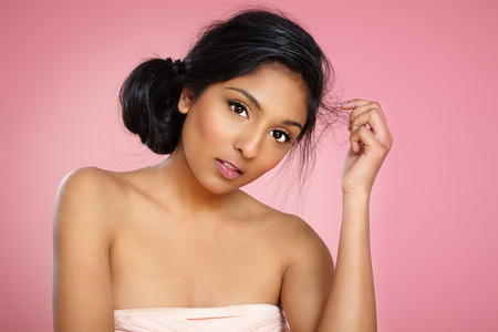 cocktail dress: Young Indian woman on pink background wearing cocktail dress.