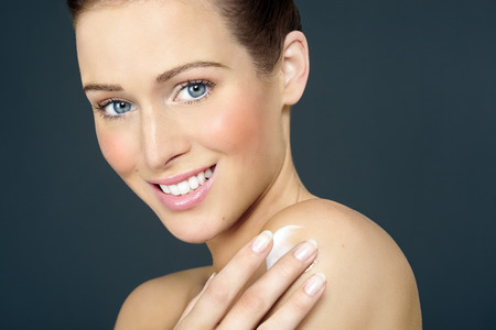 Young Caucasian woman with blue eyes applying cream to her shoulder.