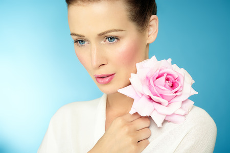 brown hair blue eyes: Young Caucasian woman with large pink rose on blue background. Stock Photo