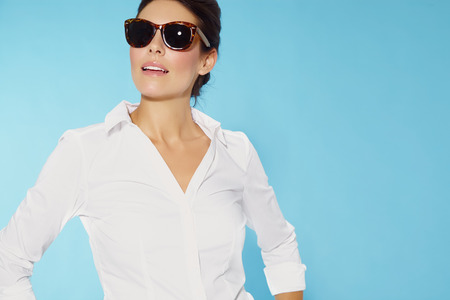 Woman wearing sunglasses and white shirt.