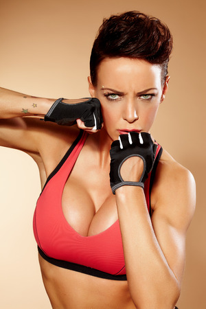 aggressive people: Sexy woman wearing training clothes and posing in aggressive way.