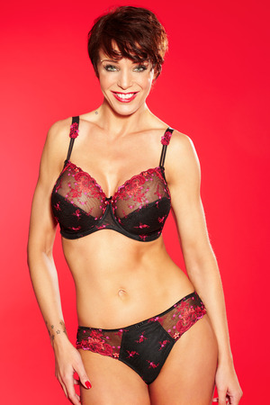 red lingerie: Muscular fit woman wearing lace lingerie set on red background.