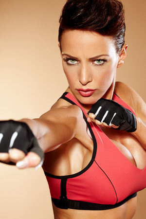 short gloves: Sexy woman wearing training clothes and posing in aggressive way.