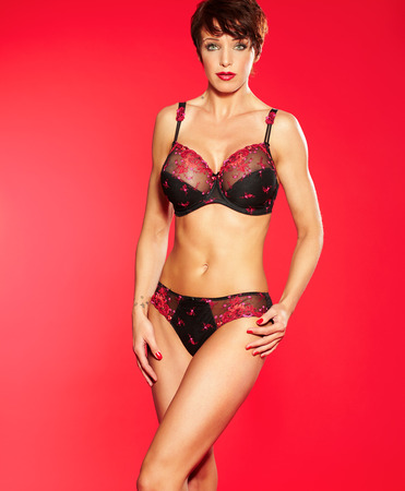 woman short hair: Muscular fit woman wearing lace lingerie set on red background.
