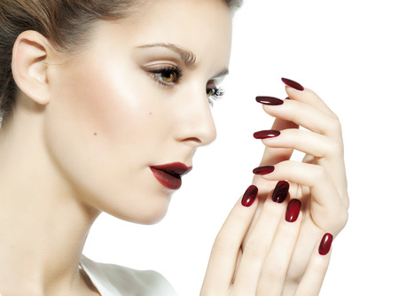 polish: Closeup of a woman with dark red lips and nails.