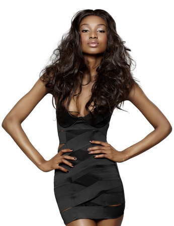 African young woman with long hair wearing small bandage black dress on white background.