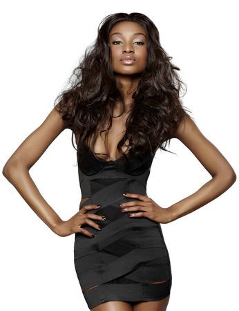 modelos negras: Joven mujer africana con el pelo largo que llevaba vestido negro peque�o vendaje en el fondo blanco.