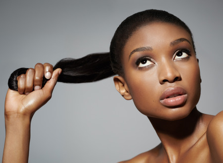 African woman holding her pony-tail in hand. Can be used for haircare or other beauty concepts. Stock Photo