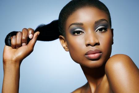 Femme africaine tenant sa queue de cheval en main. Peut être utilisé pour le soin des cheveux ou d'autres concepts de beauté. Banque d'images - 37773813