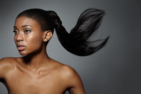 black hair: Mujer africana hermosa con el pelo largo flotando. Foto de archivo