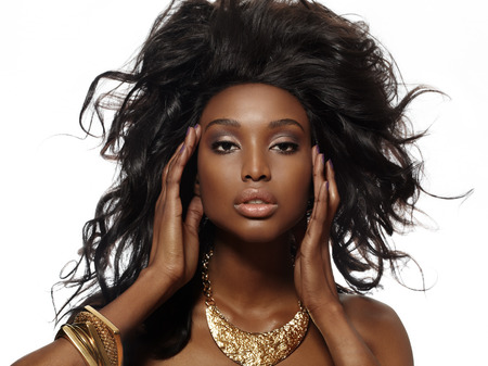 African model with large hairstyle posing in golden jewelry.