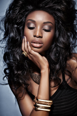 black hair woman: African woman with long styled hair wearing jewelry.
