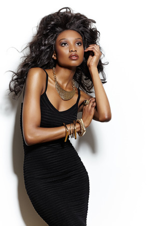 Dark fashion model with big hair posing at white wall. Фото со стока