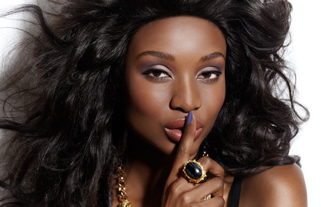 Closeup of a beautiful glamourous dark woman wearing large ring and making a silence gesture.