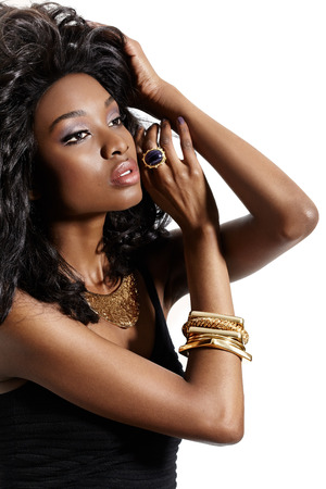 upper class: African model with large hairstyle posing in golden jewelry.