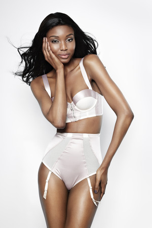 black and white image: African model wearing pink silk lingerie set.