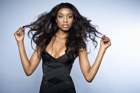 青の背景に黒包帯ドレスを着て長い髪を持つアフリカの若い女性。それはネイティブ解像度と組成は copyspace の青のグラデーションを許可するように