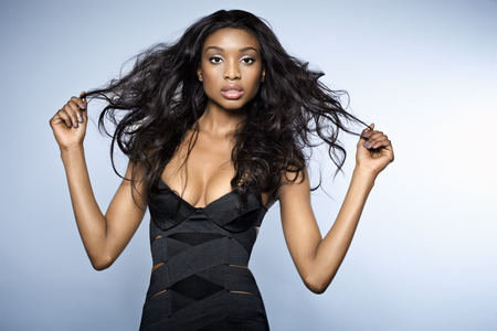 cocktail dress: African young woman with long hair wearing small bandage black dress on blue background. It is native resollution, and the composition was originally shot like this, to allow blue gradient for copyspace. Stock Photo