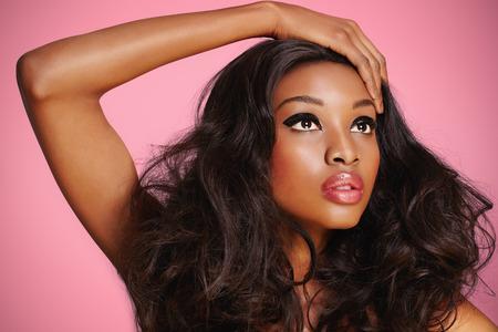 black hair: Modelo africana con maquillaje agradable en el fondo de color rosa.