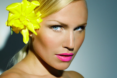 tanned: Closeup of a tanned woman with bright pink lips and yellow tulip in her hair.