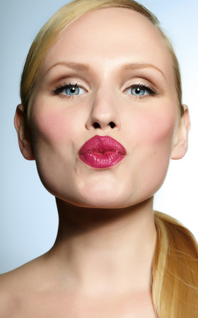 mouth kiss mouth: Young woman with bright lipstick making a kissing pout.