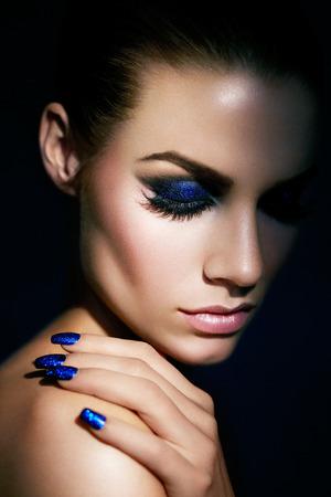 Model wearing blue glittery manicure and eye-shadow. Banco de Imagens - 37773460
