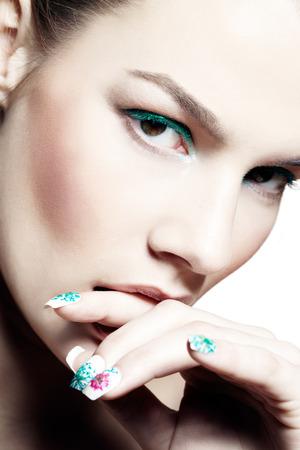 nailart: Closeup of a model with cyan eyeshadow and matching nail-art.