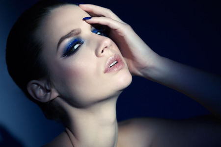 glitter makeup: Model wearing blue glittery manicure and eye-shadow. Stock Photo