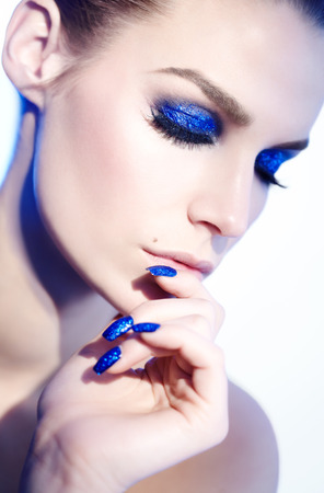 glitter makeup: Closeup of a model with blue glitter makeup and manicure. Lighting is 90s style and model looks slightly like a famous 90s model.