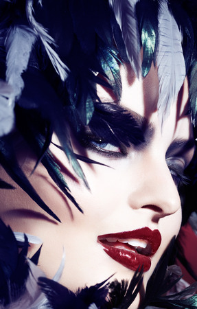 gothic woman: Closeup of a woman with gothic makeup and dark feathers. Stock Photo