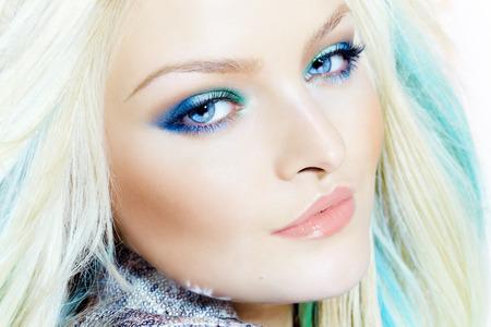 rubia ojos azules: Primer plano de una mujer hermosa que lleva maquillaje en tonos fríos y para el cabello, extensiones de colores. Foto de archivo