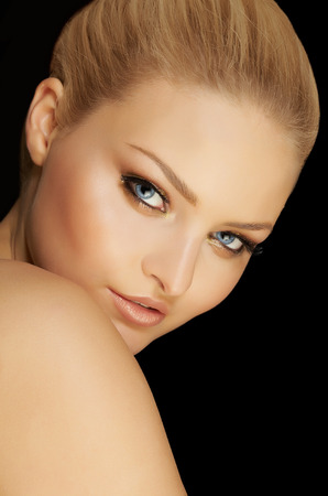 blonde  blue eyes: Closeup of a young woman on black background.