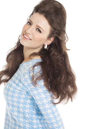 sixties: Sixties fashion woman in light blue outfit with retro hairstyle and makeup smiling over white background.