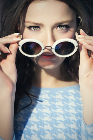 sixties: Closeup of a young woman in sixties retro style with old-fashioned sunglasses under bright spotlight.