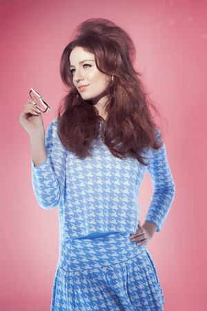 60s fashion: Retro sixties style girl with long hair posing over pink studio background with blue outfit and sunglasses. Bright light and fashion allure. Stock Photo