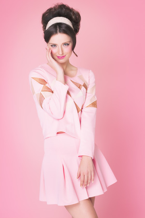 pink posing: Sixties fashion woman in soft pink outfit with retro hairstyle and makeup posing over pink background. Stock Photo