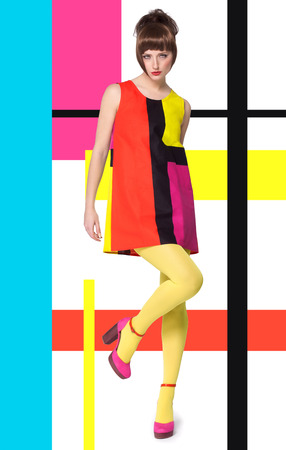 Colorful concept in sixties retro fashion style with Caucasian model posing full body over designed background with colorful bright stripes and color blocks.