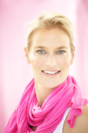 40 year old woman: Caucasian 40 year old woman wearing pink scarf. Stock Photo